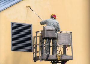 Commercial Painter in Gray Suit Standing in Lifting Platform and Painting Exterior Wall Beige