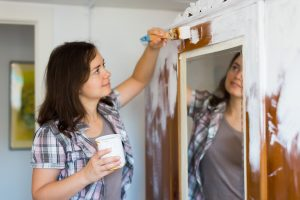 Woman Painting Mirror Wall in Closet